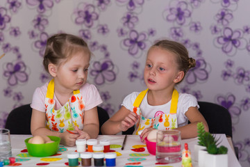 Girls are preparing for the Easter holiday, color eggs