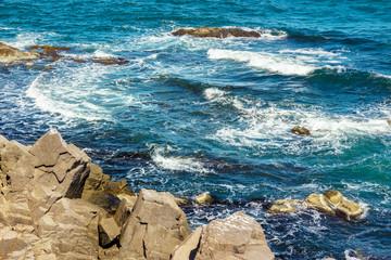 sea waves breaks about rocky shore