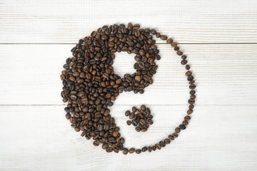 Top view of coffee beans making a symbol Yin yang on light wooden surface