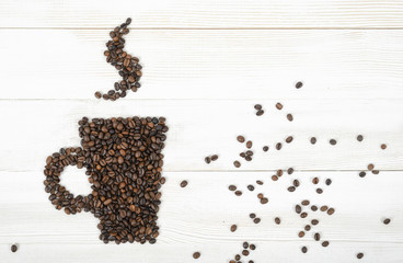 Top view coffee beans making a shape of cup on wooden surface