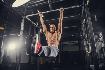 A man doing stomach exercises on a horizontal bar.