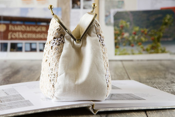 Handmade embroidery handbag with metal clasp on the opened book