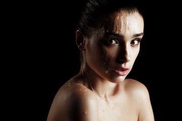 Beauty Portrait of Young Woman with Strobing Makeup Liquid on Face. Wet Body Effect. Strobing Highlighting technique. Professional Retouch. Studio Photo. Ideal commercial concept. Black background
