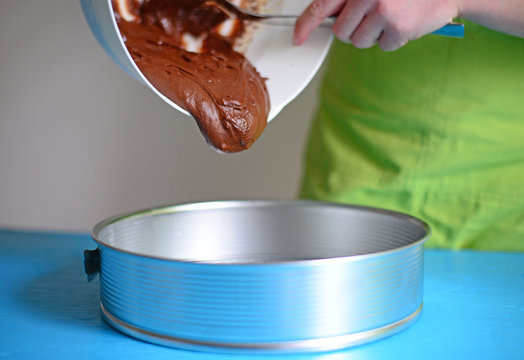 Pouring fresh chocolate cream in metal mould for cake