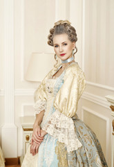 Beautiful woman in historical dress in Baroque style in the inte
