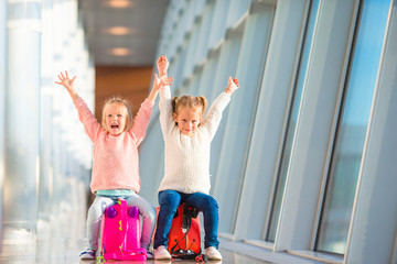 Adorable little girls having fun in airport sitting on suitcase waiting for flight