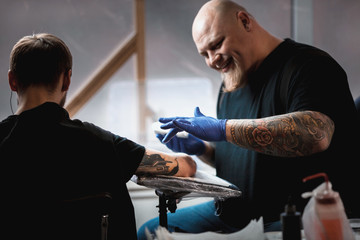 master tattoo artist with a beard makes gloves tattoo on hand men
