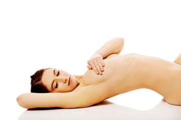 Beautiful naked slim woman lying on the floor