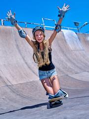 Teen skateboarding his skateboard hands up outdoor. Girl do  stunt .