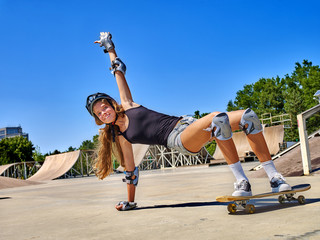 Teen girl rides his skateboard outdoor. Girl do  stunt aganist blue sky. Summer sports.
