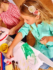 Group little girl wearing green  with brush painting on table in  kindergarten . Top view.