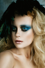 Beautiful girl in the image of bird with bright makeup,  gold ha
