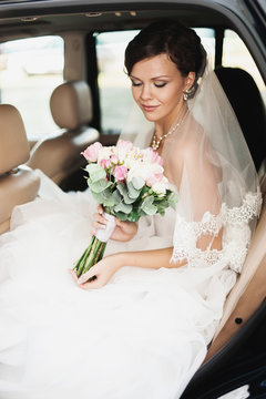 Wedding day. Bride is sitting and smiling in a car with wedding