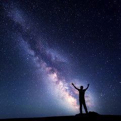 Landscape with colorful Milky Way. Night sky with stars and silhouette of a happy man with raised up arms on the mountain. Beautiful Universe. Space background