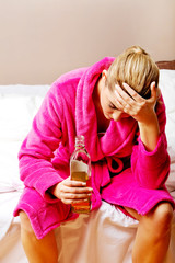 Young worried woman drinking alcohol in bed