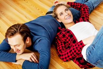 Young happy couple lying on the floor