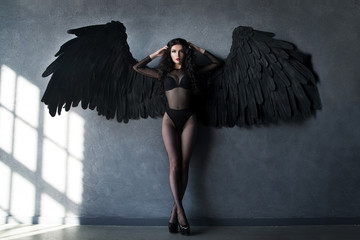 Fallen black angel with wings. Sexual woman