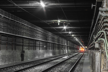 Empty subway tunnel, train at the end of the tunnel