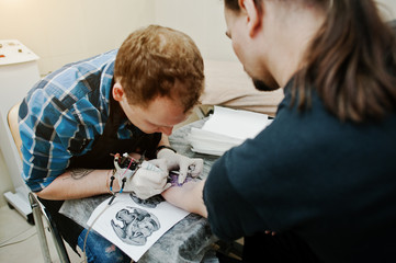 Tattoo master make tattoo for rocker man at tattoo salon
