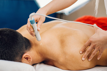 Laser treatment in physical therapy. Therapist using low intensity laser beam to treat patient