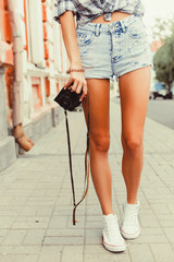 yOutdoor crop foot of tanned slim woman with camera,travel photo.Adventure,hiker,sneakers,shorts,old city street,freedom concept