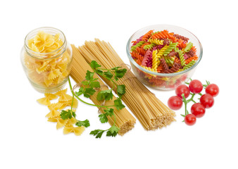 Several different uncooked pasta, sprigs of parsley and cherry t