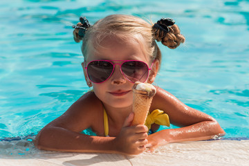 happy little girl in sunglasses eating ice cream in the pool