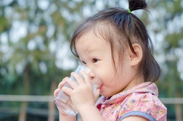 Little Asian girl drinking water from glass