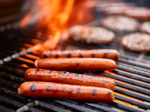 tasty hot dogs cooking on grill with hamburgers