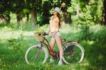 Young pretty sensual blond girl posing outdoor  with red vintage bicycle in a blue shirt in white sneakers, fashionable stylish clothes sunglasses red lipstick on her lips