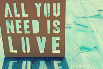 Inspirational quote, all you need is love, on blue wooden background. Vintage effect applied