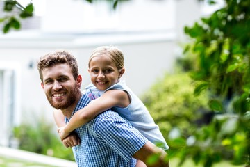 Smiling father carrying daughter while standing in yard