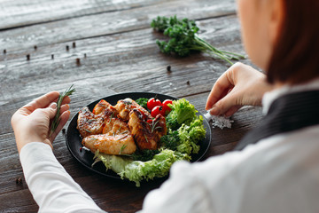 Wall Mural - Decoration of chicken wings on wooden table. Chief prepares grilled spicy chicken with fresh vegetables. Over the shoulder view on food decoration.