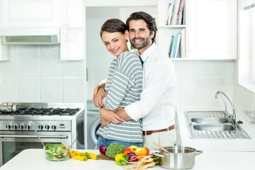 Couple embracing while preparing food in kitchen
