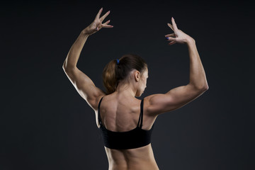 Attractive fitness woman on gray background in studio. Muscular back close-up
