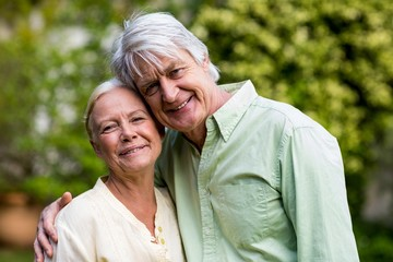 Smiling senior couple standing in yard