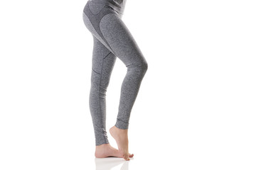 Close up side sexy view of woman legs stretching the muscles of the foot in gray sports thermal underwear with pattern.