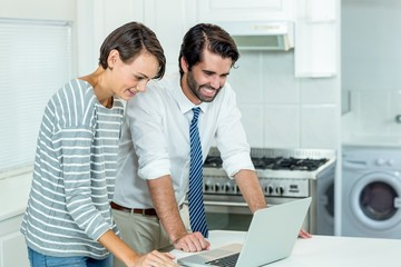 Couple looking in laptop while standing by table in kitchen