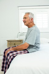 Senior man on bed at home