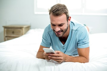 Happy man using cellphone on bed