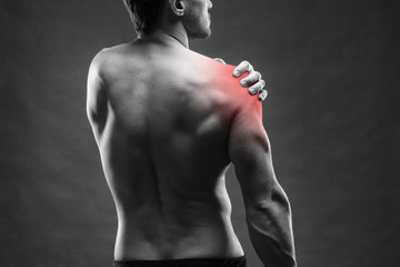 Pain in the shoulder. Muscular male body. Handsome bodybuilder posing on gray background