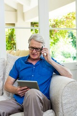 Senior man using mobile phone with digital tablet at home