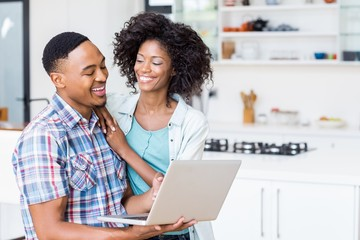 Happy young couple using laptop in kitchen
