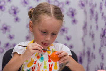 Girl paints paints eggs for Easter