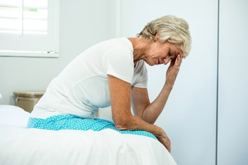 Tensed aged woman sitting on bed