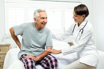 Smiling female doctor assisting senior man