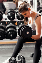 Professional athletic woman pumping up muscules with big heavy dumbbells in gym interior. Strong woman crossfit workout with dumbbell in gym, biceps exercise closeup.