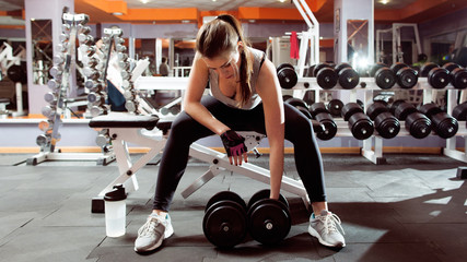 Professional athletic woman pumping up muscules with dumbbells in gym interior. Strong woman crossfit workout with dumbbell in gym, biceps exercise closeup.