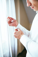 Stylish and handsome groom in waistcoat tying his bow-tie in the morning of the wedding day.