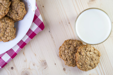 Plate with oatmeal cookies and glass of milk